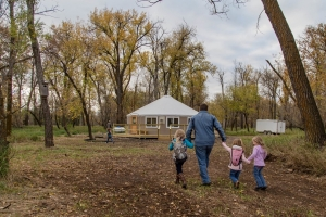 A family approaching a yurt accommodation in North Dakota